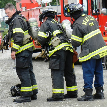 Firefighters help each other with their air bottles at the S. Monroe fire on June 18, 2012. (Photo by Lisa Swenson)