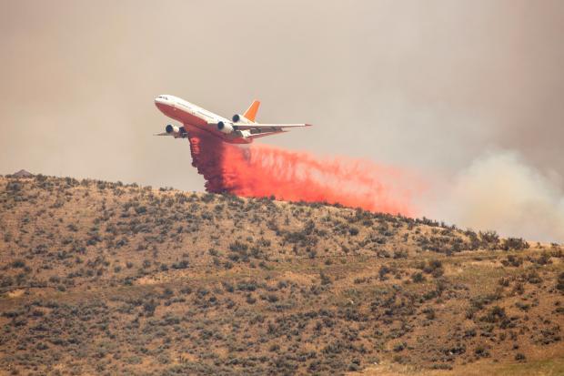 A DC-10 dropping retardant down below [Photo Courtesy: inciweb]